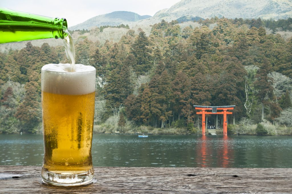 Beer poured into a glass with a Japanese background