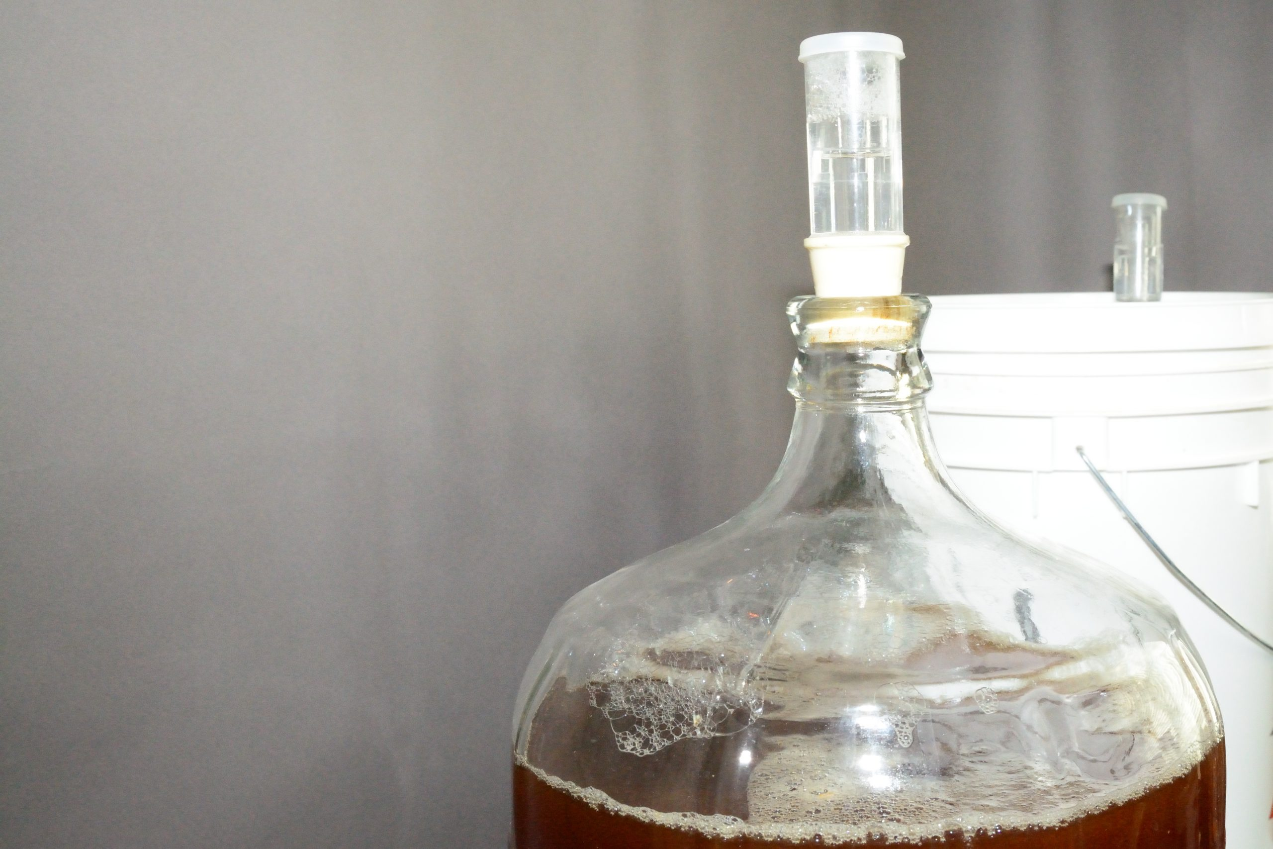 5 gallon glass carboy filled with beer