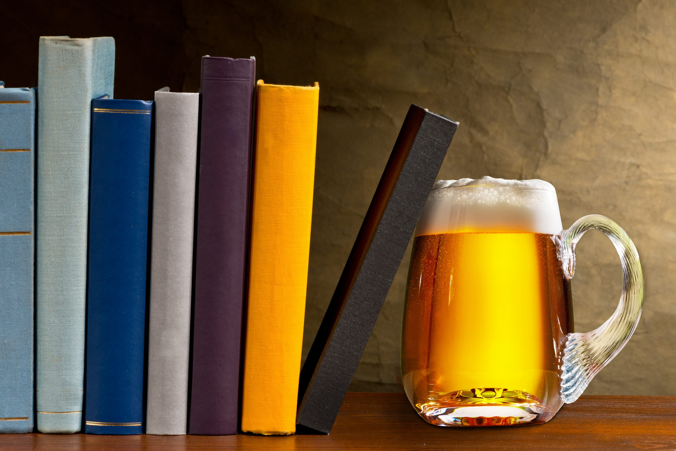 glass of beer next to books