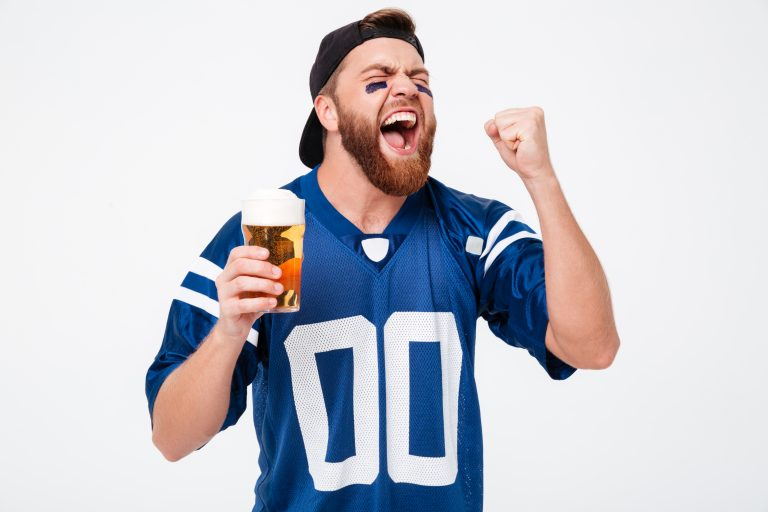 Excited fan drinking a beer