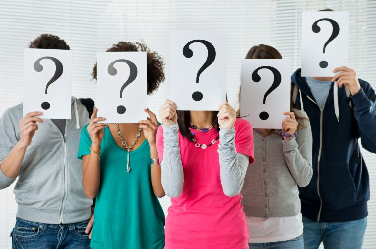 students covering face with question marks