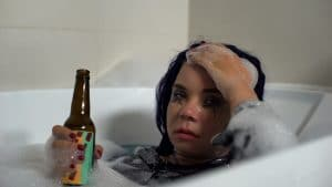 drunk womon with beer bottle in a bath tub