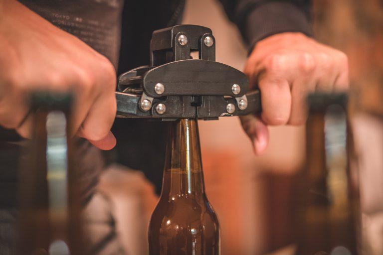 putting bottle caps on a beer bottle